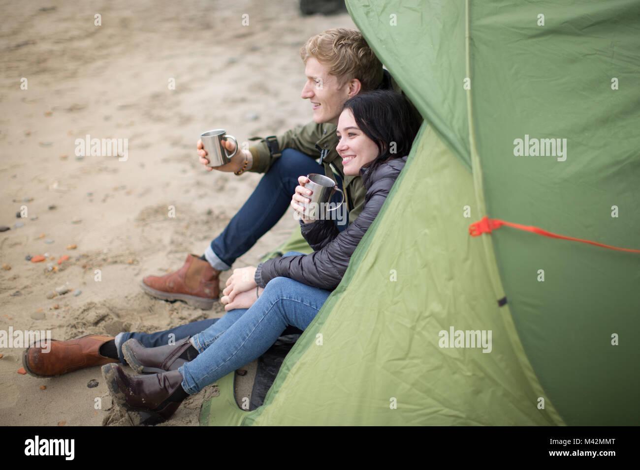 Coppia giovane camping sulla spiaggia in autunno Immagini Stock