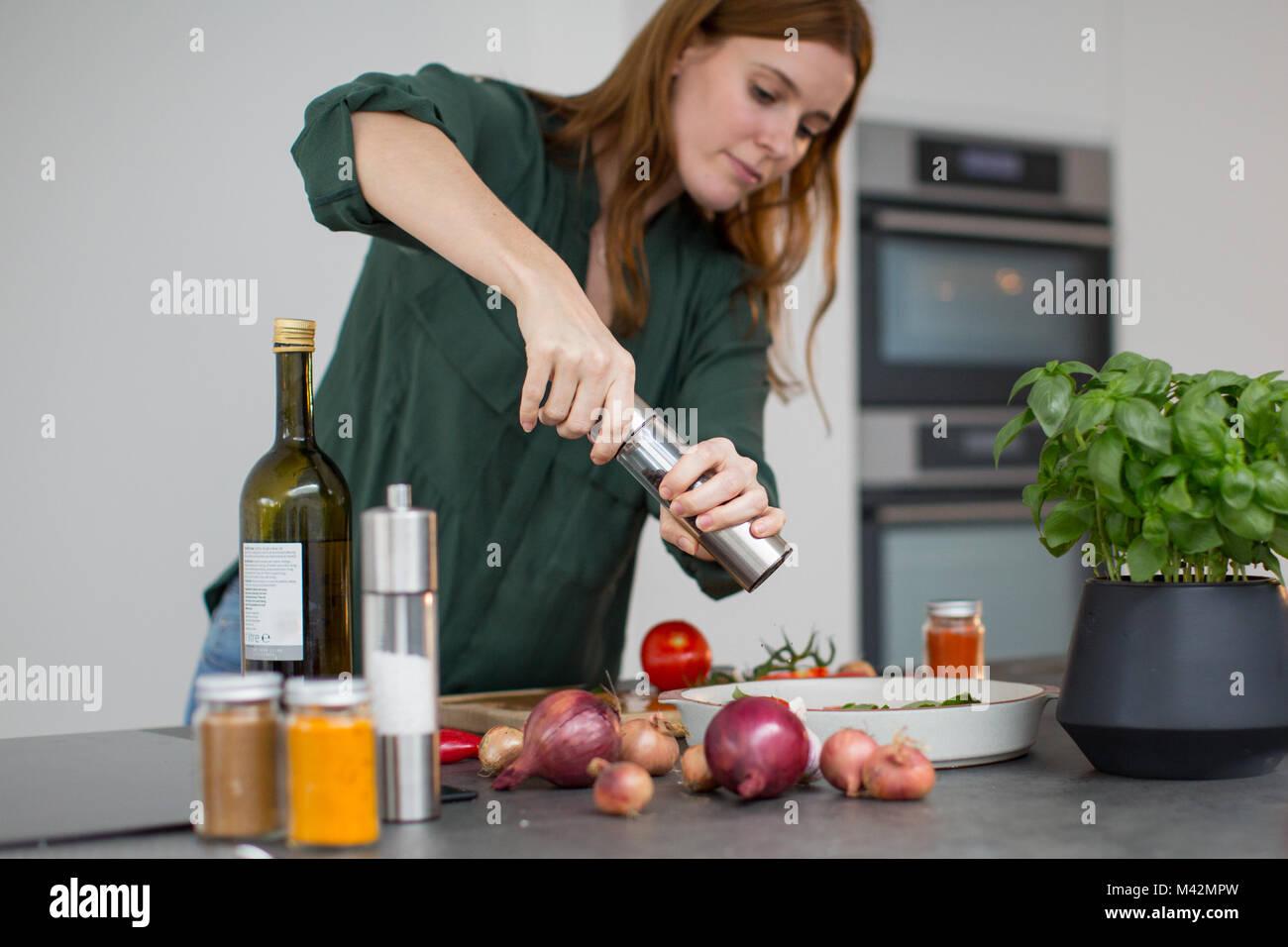 Femmina adulta condimento un piatto Immagini Stock