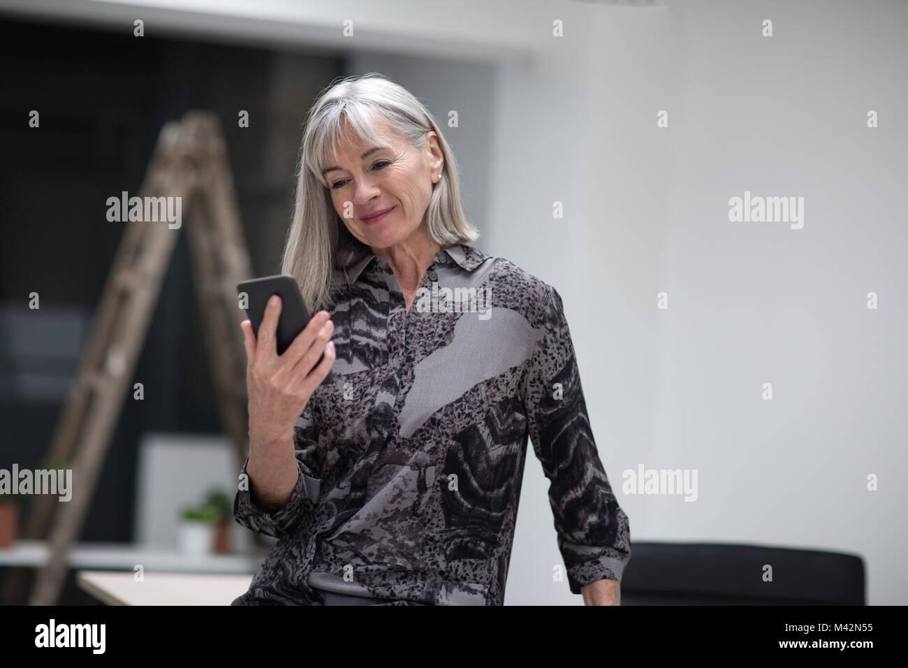 Senior imprenditrice utilizza lo smartphone Immagini Stock