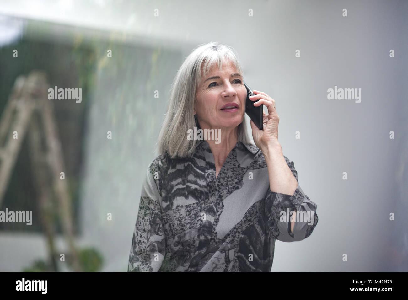 Senior imprenditrice sullo smartphone Immagini Stock