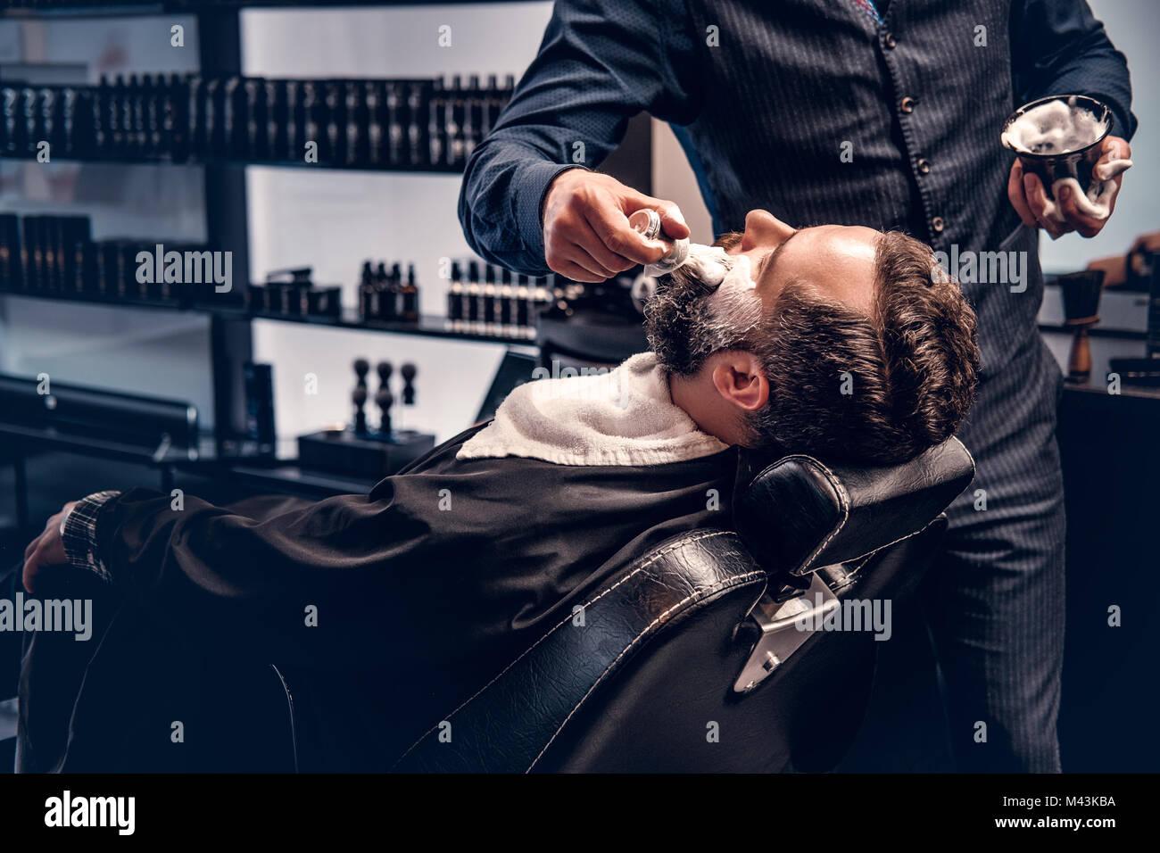 Il barbiere si applica alla schiuma da barba Immagini Stock