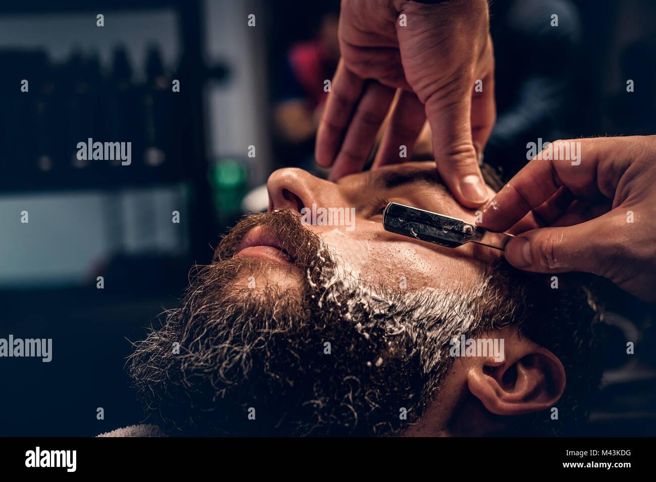 Barbiere di rasatura maschio barbuto con un rasoio affilato. Immagini Stock