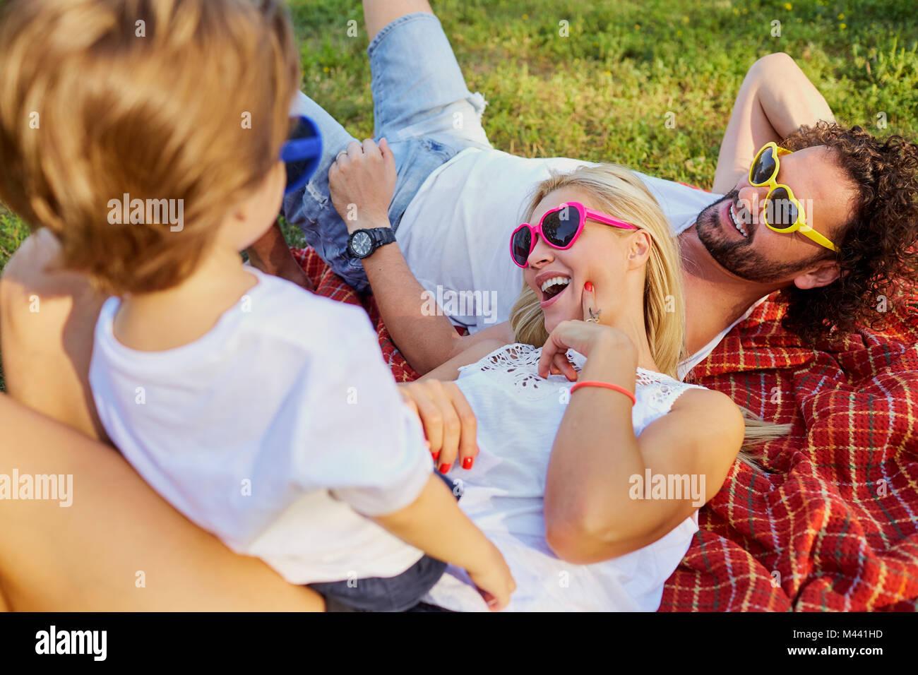 La famiglia felice che giocano nel parco. Immagini Stock