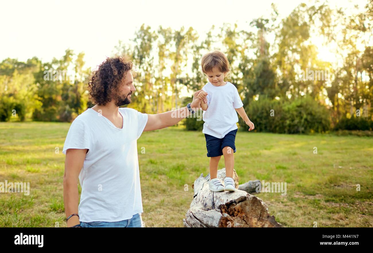 Padre giocando con suo figlio nel parco. Immagini Stock