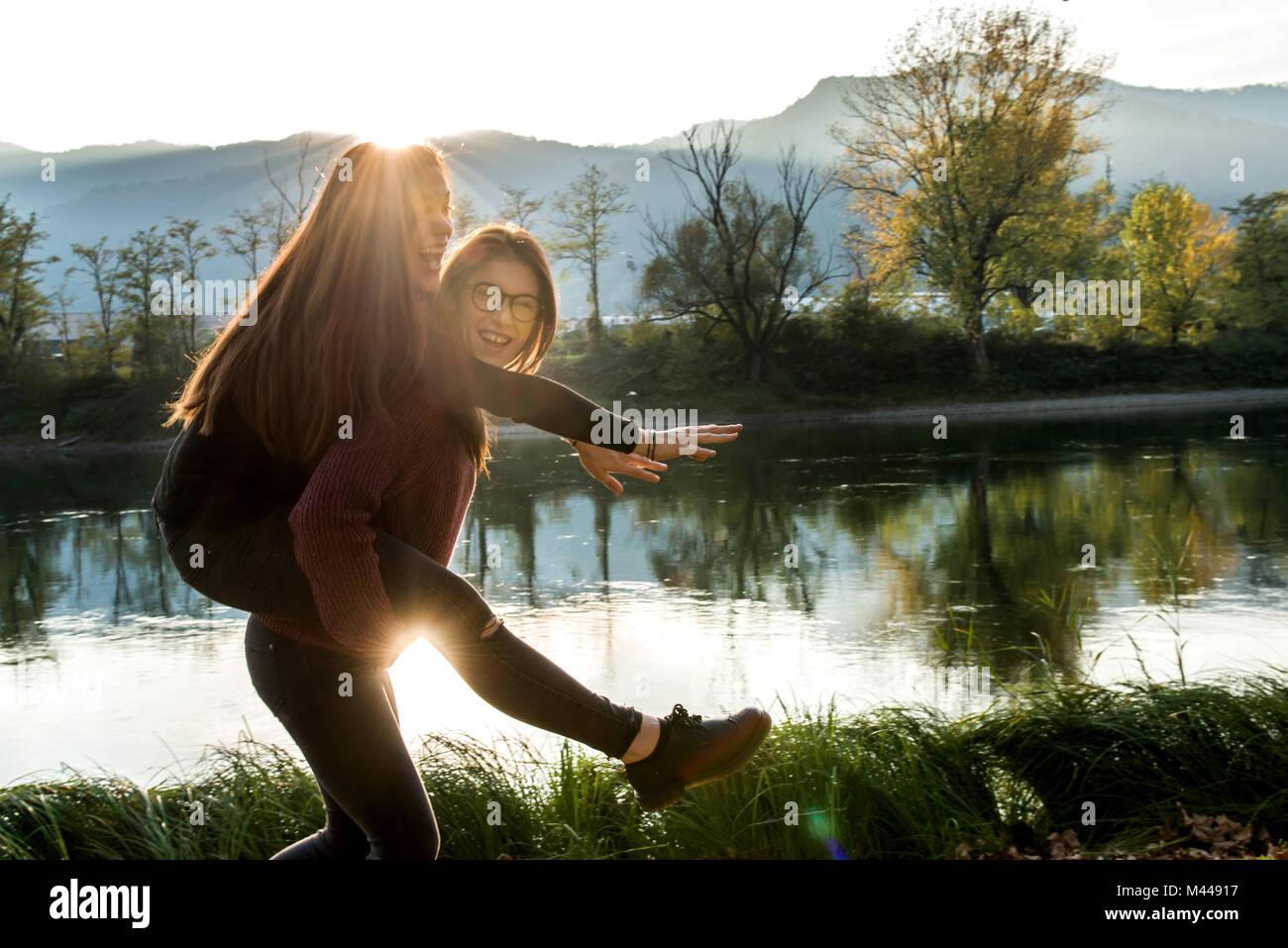 Giovane donna dando migliore amico piggy back sul lungofiume, Calolziocorte, Lombardia, Italia Immagini Stock