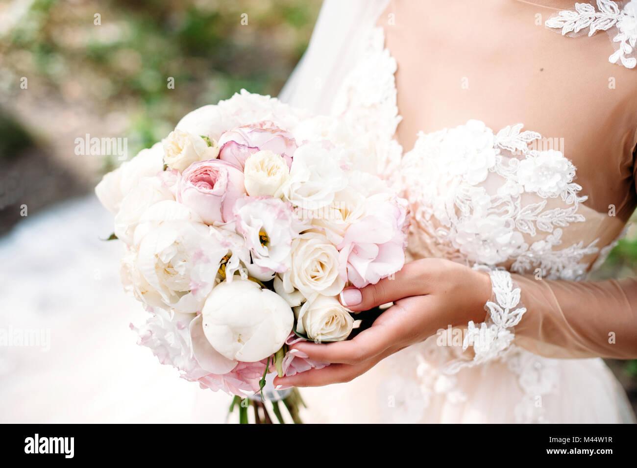 Sposa matrimonio holding peonia bouquet nelle vostre mani. Bianco e fiori di colore rosa. Close-up Foto Stock