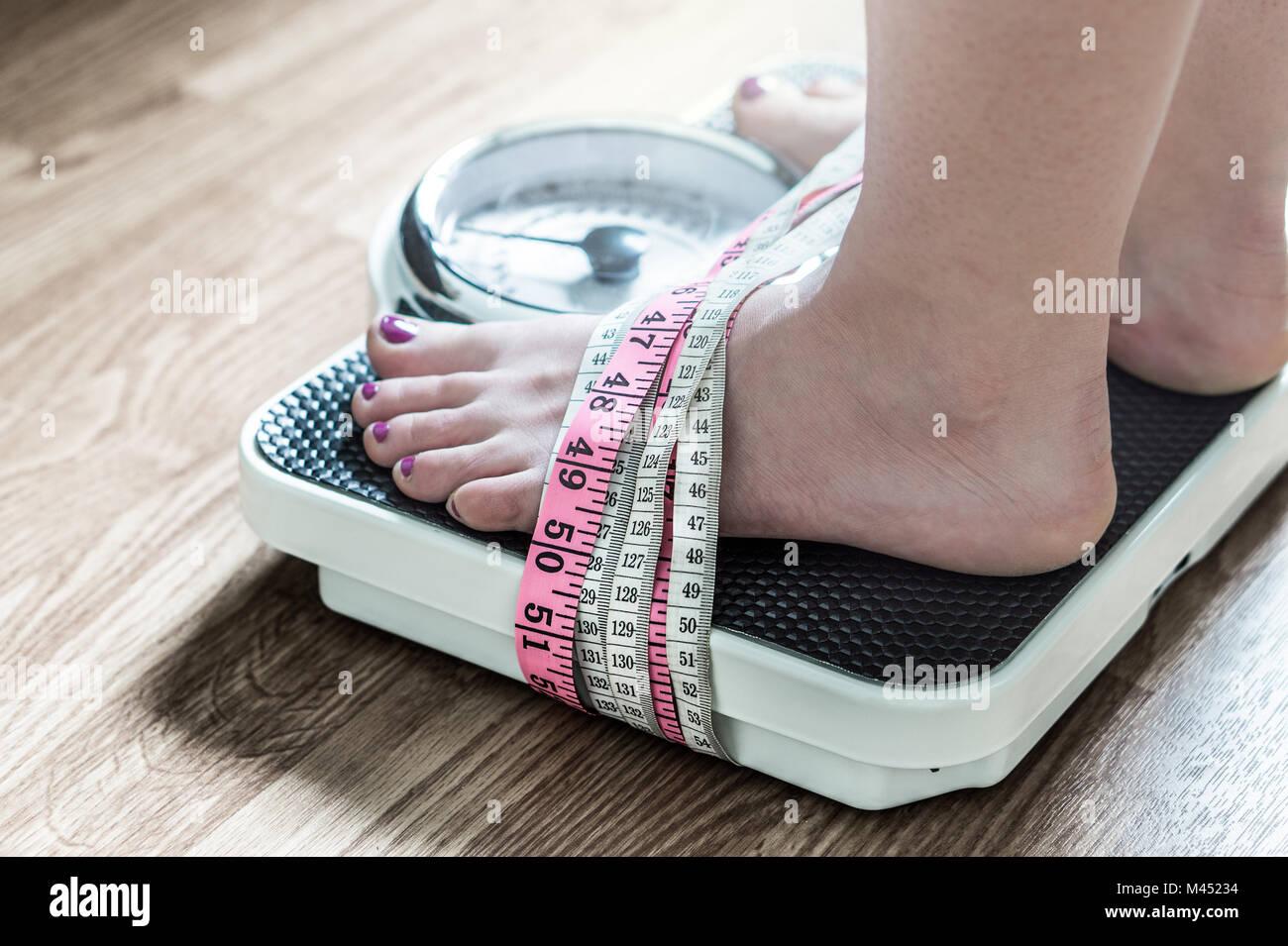 I piedi legati con nastro di misurazione a una scala di peso. Dipendenza e ossessione per la perdita di peso. Anoressia Foto Stock