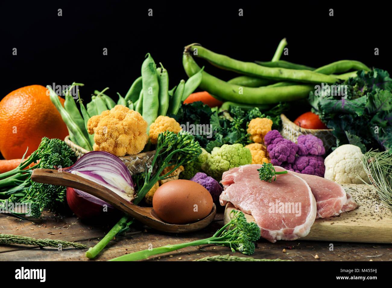 Un mucchio di alcuni frutti e alcune diverse verdure crude, come i cavolfiori di diversi colori, broccolini o fagiolini, e qualche uova e qualche sl Foto Stock