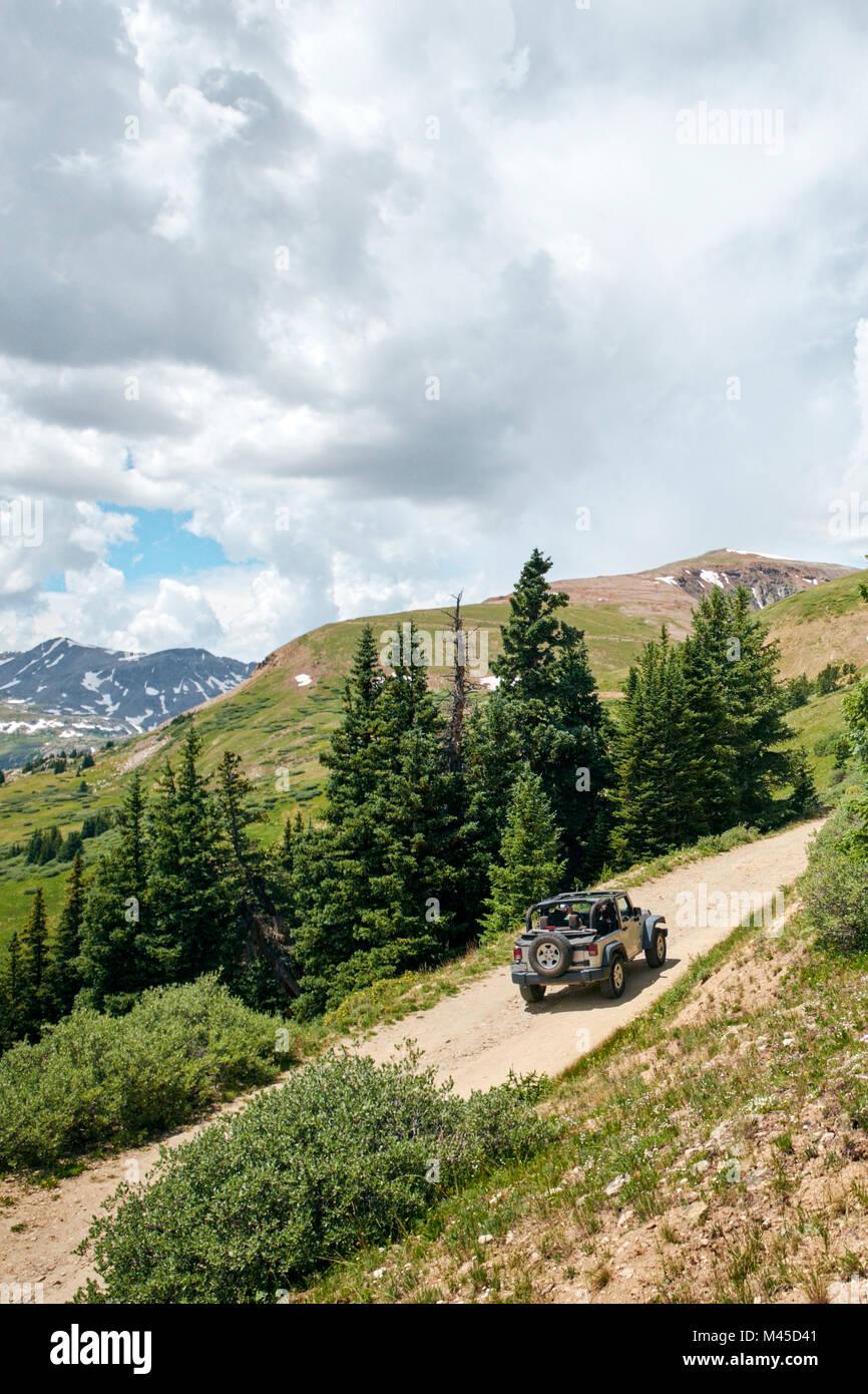 Viaggio giovane convertibile di guida fuoristrada su rurale strada di montagna, Breckenridge, Colorado, STATI UNITI Foto Stock