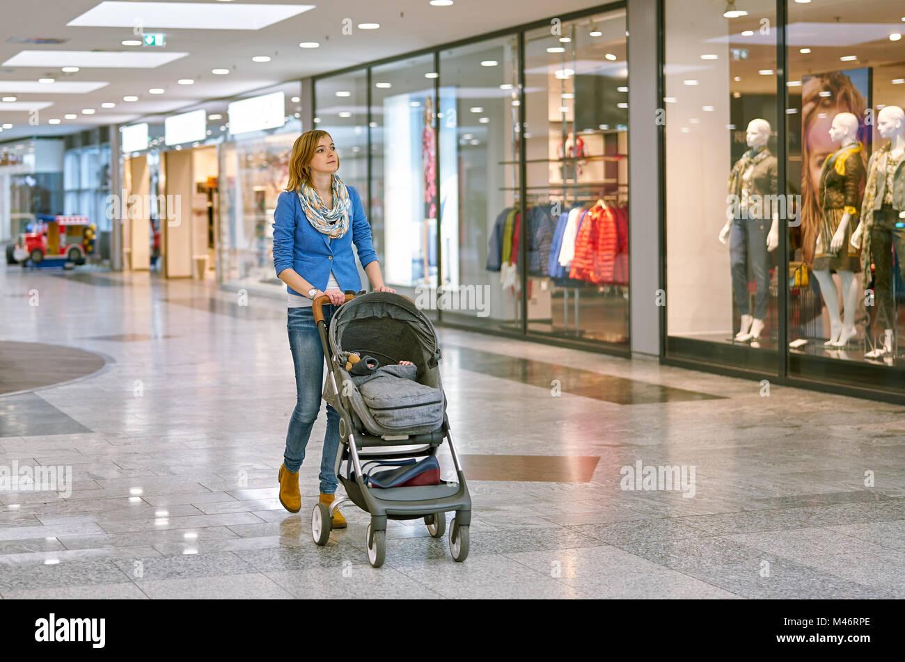 Giovane Donna con bambino durante lo shopping Immagini Stock