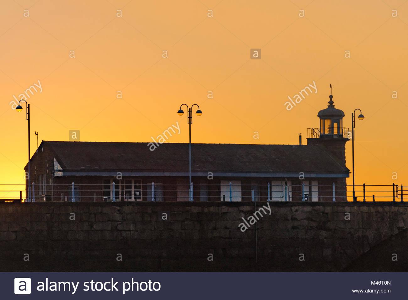 Il vecchio edificio del terminal si stagliano contro un arancione tramonto presso il molo di pietra, Morecambe Immagini Stock