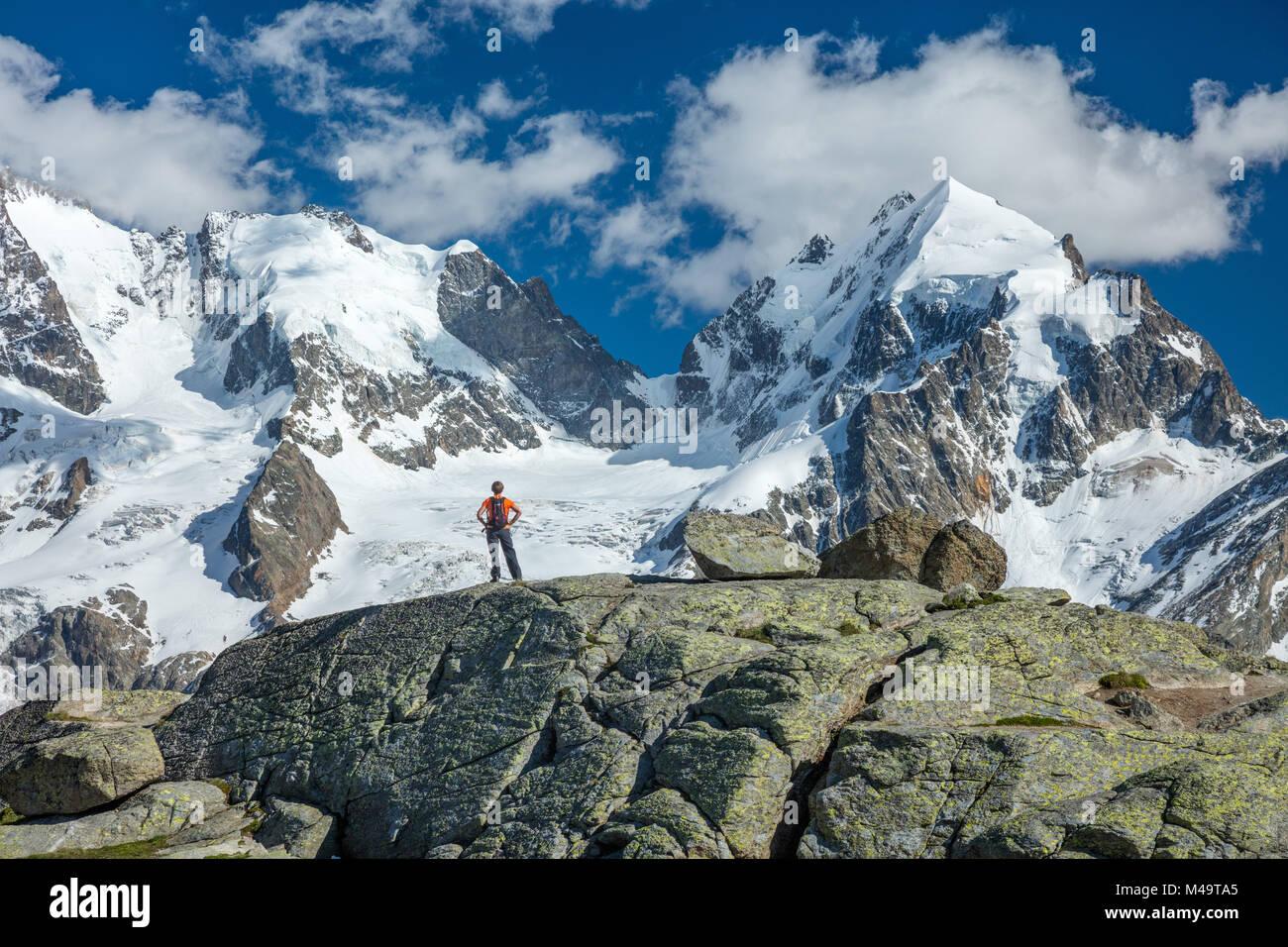 Escursionista sotto il Piz Bernina e Piz Rosbeg, Fuorcla Surlej, Berniner Alpi, Grigioni, Svizzera. Immagini Stock