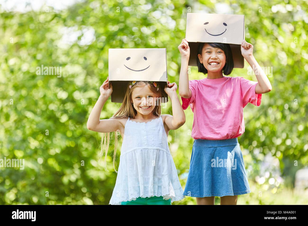 Due ragazze giocare con divertenti dipinto di scatole di cartone in estate in natura Immagini Stock