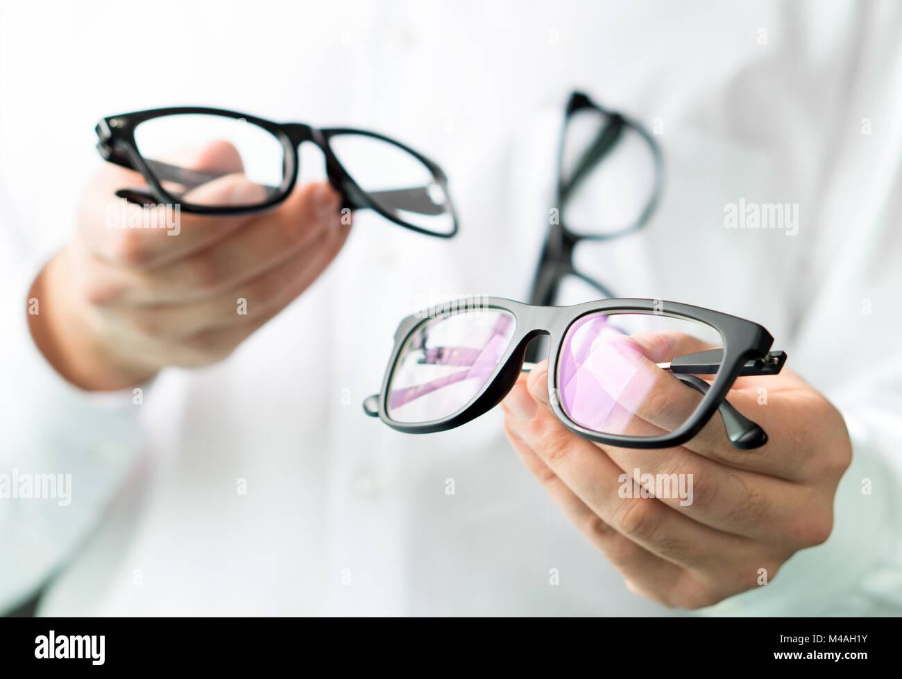 Ottico confrontando le lenti o che mostra il cliente diverse opzioni in occhiali. Occhio medico mostra nuovi occhiali. Immagini Stock