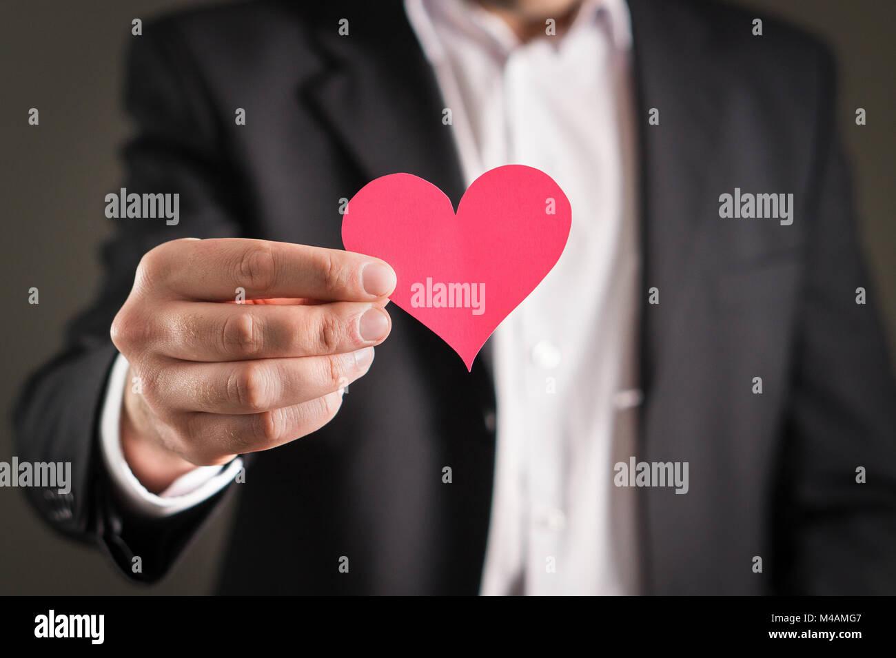 Uomo in un vestito e un cartone cuore di carta. Imprenditore o fidanzata con un simbolo d'amore. Proposta, matrimoni, Immagini Stock