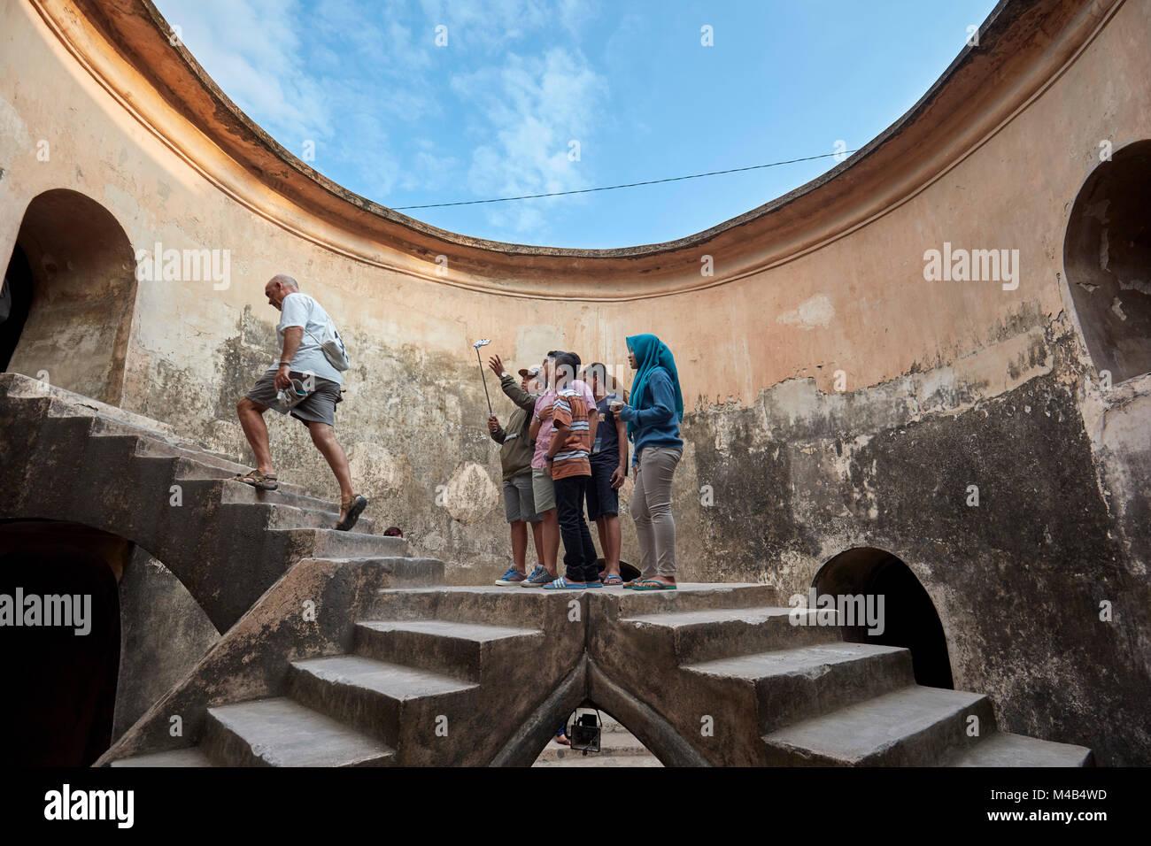 I turisti in Gumuling ben (Sumur Gumuling), uno-storeyed struttura circolare, una volta usato come una moschea. Immagini Stock