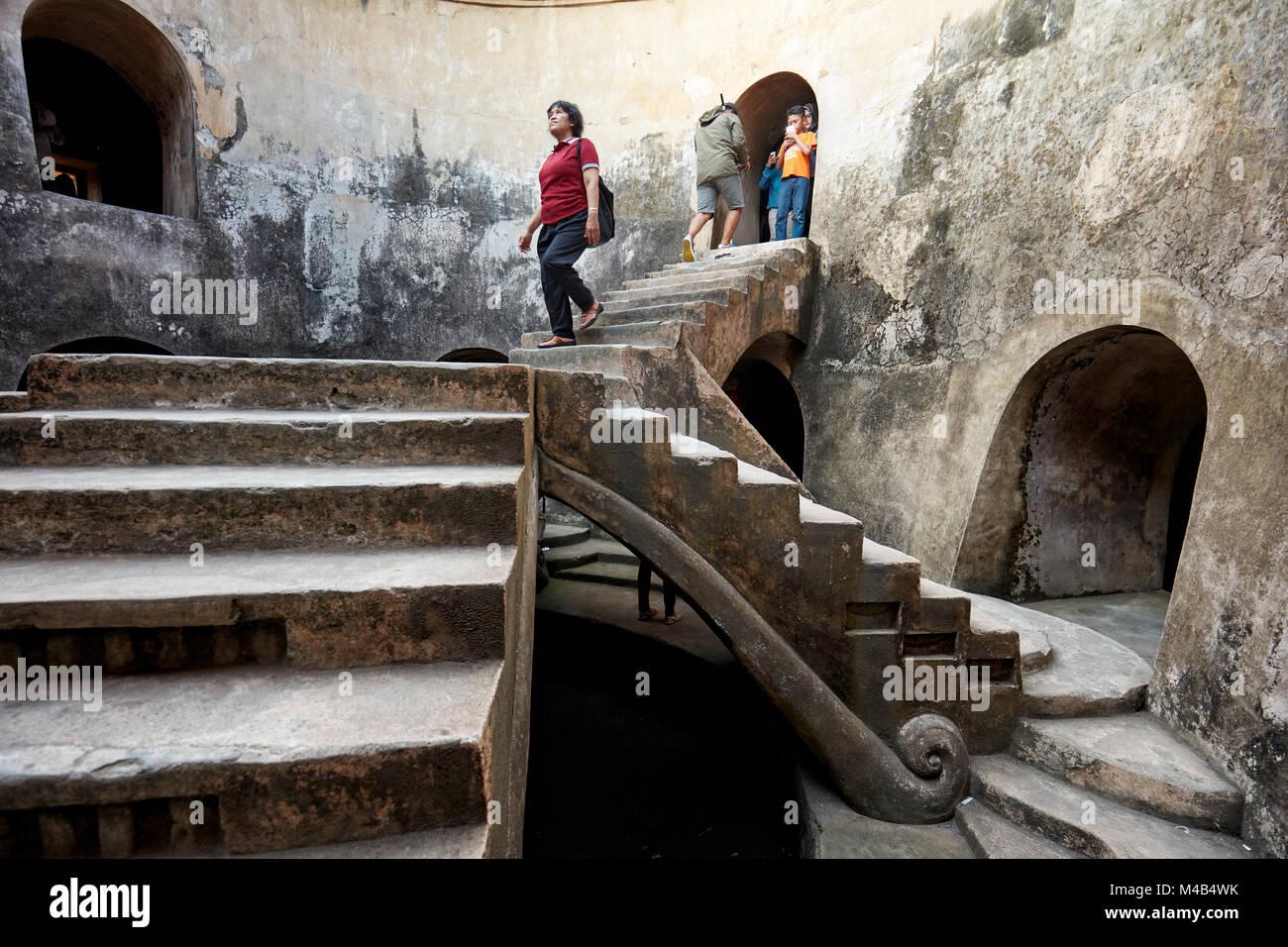 Donna in Gumuling ben (Sumur Gumuling), uno-storeyed struttura circolare, una volta usato come una moschea. Taman Immagini Stock