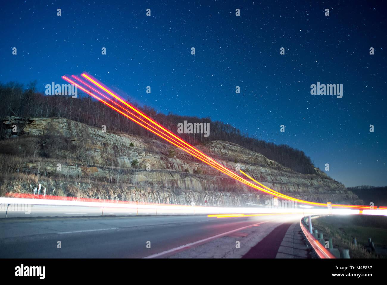 Sentieri di luce di notte in montagna dal traffico in uscita Foto Stock