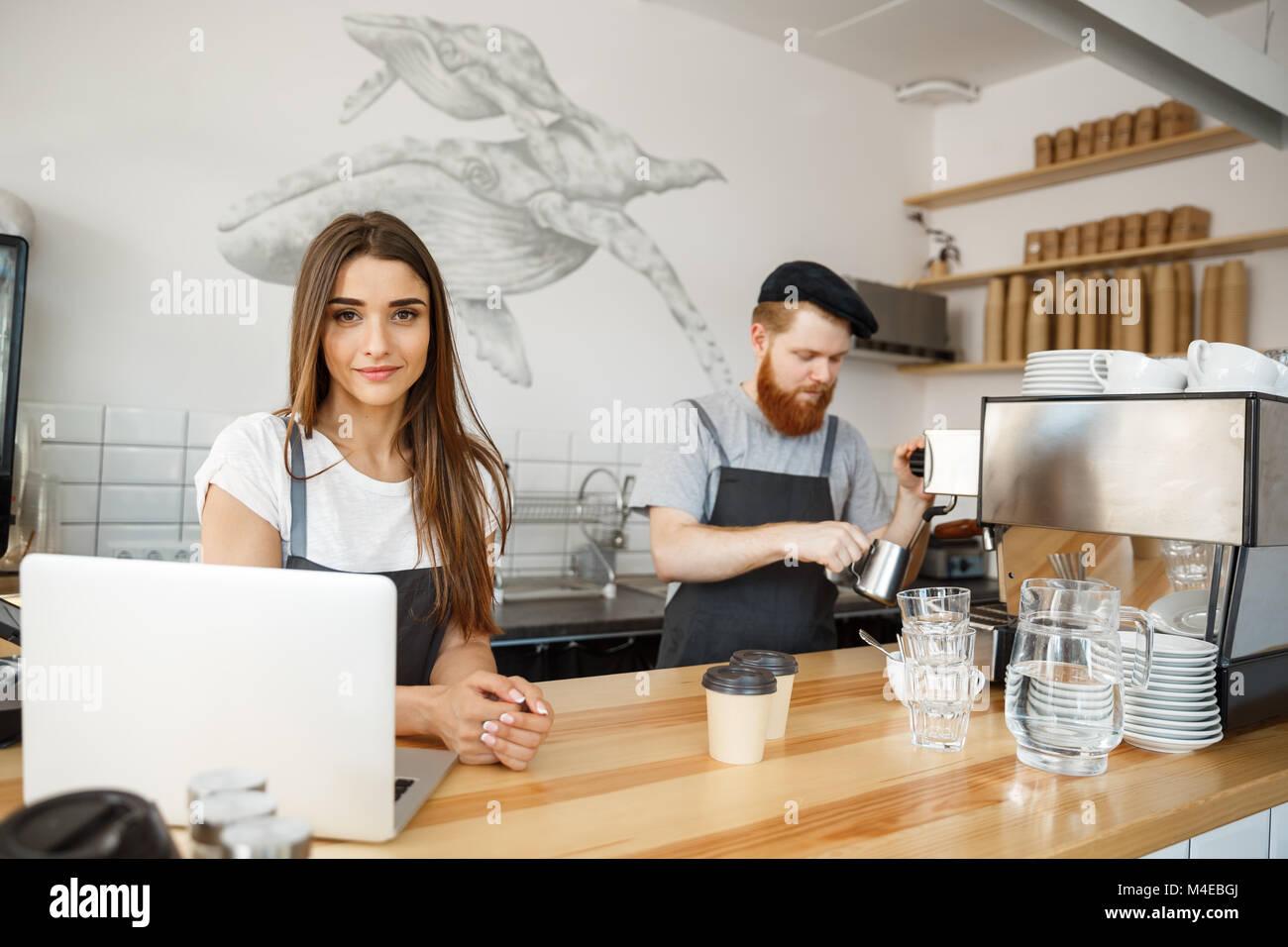 Caffè il concetto di Business - Positivo giovane uomo barbuto e bella attraente dama barista giovane amano lavorare Foto Stock