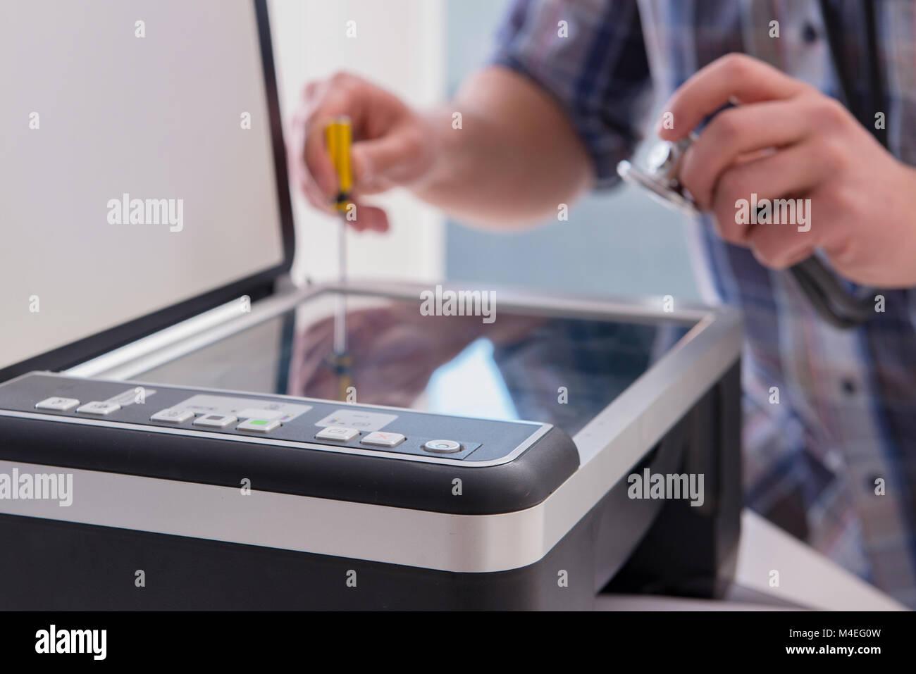 Repairman riparazione rotto stampante a colori Immagini Stock