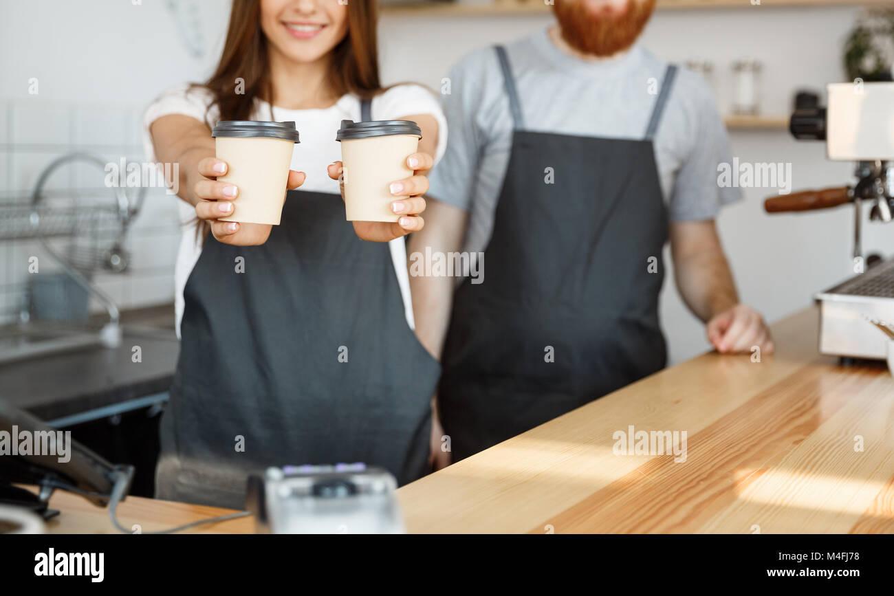 Caffè il concetto di Business - Positivo giovane uomo barbuto e bella attraente dama barista giovane dando Immagini Stock