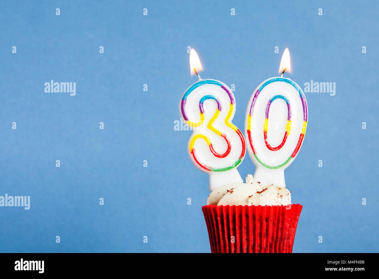 Numero 30 Compleanno Candela In Una Tortina Contro Uno Sfondo Blu