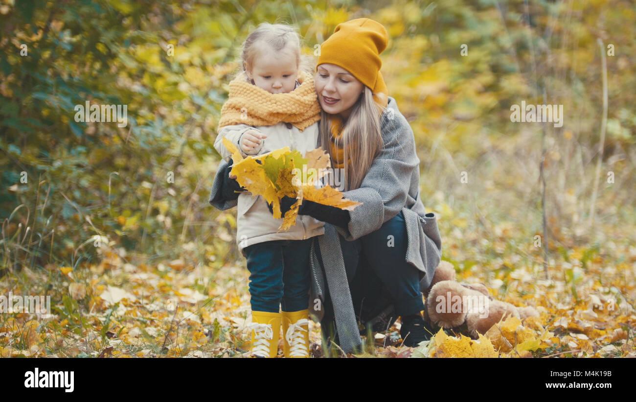 La bionda bambina con la sua mamma passeggiate nel parco di autunno - sono divertenti e raccogliere foglie, close up Foto Stock