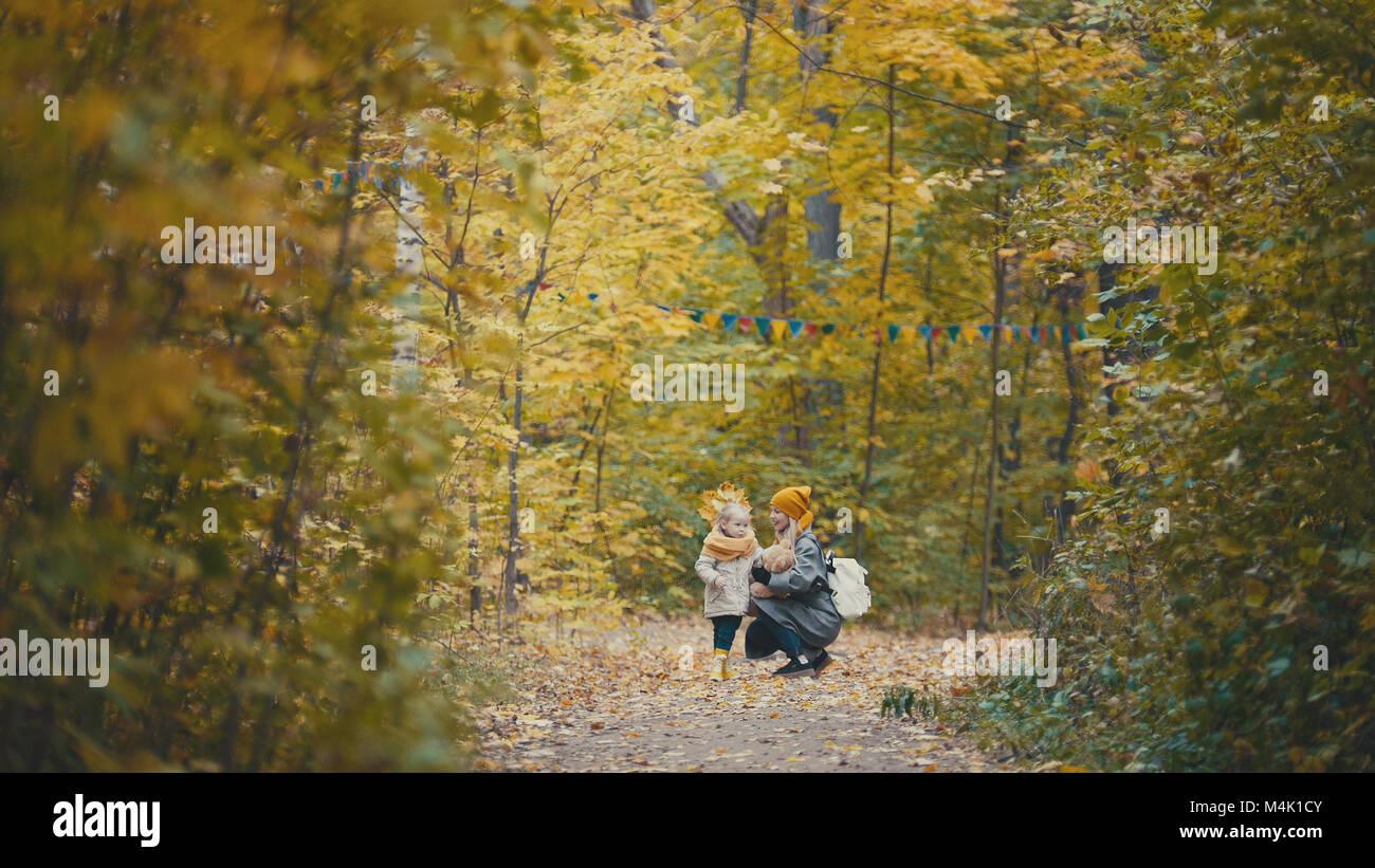 Piuttosto piccola figlia con la sua mamma passeggiate nel parco di autunno - abbraccia Foto Stock