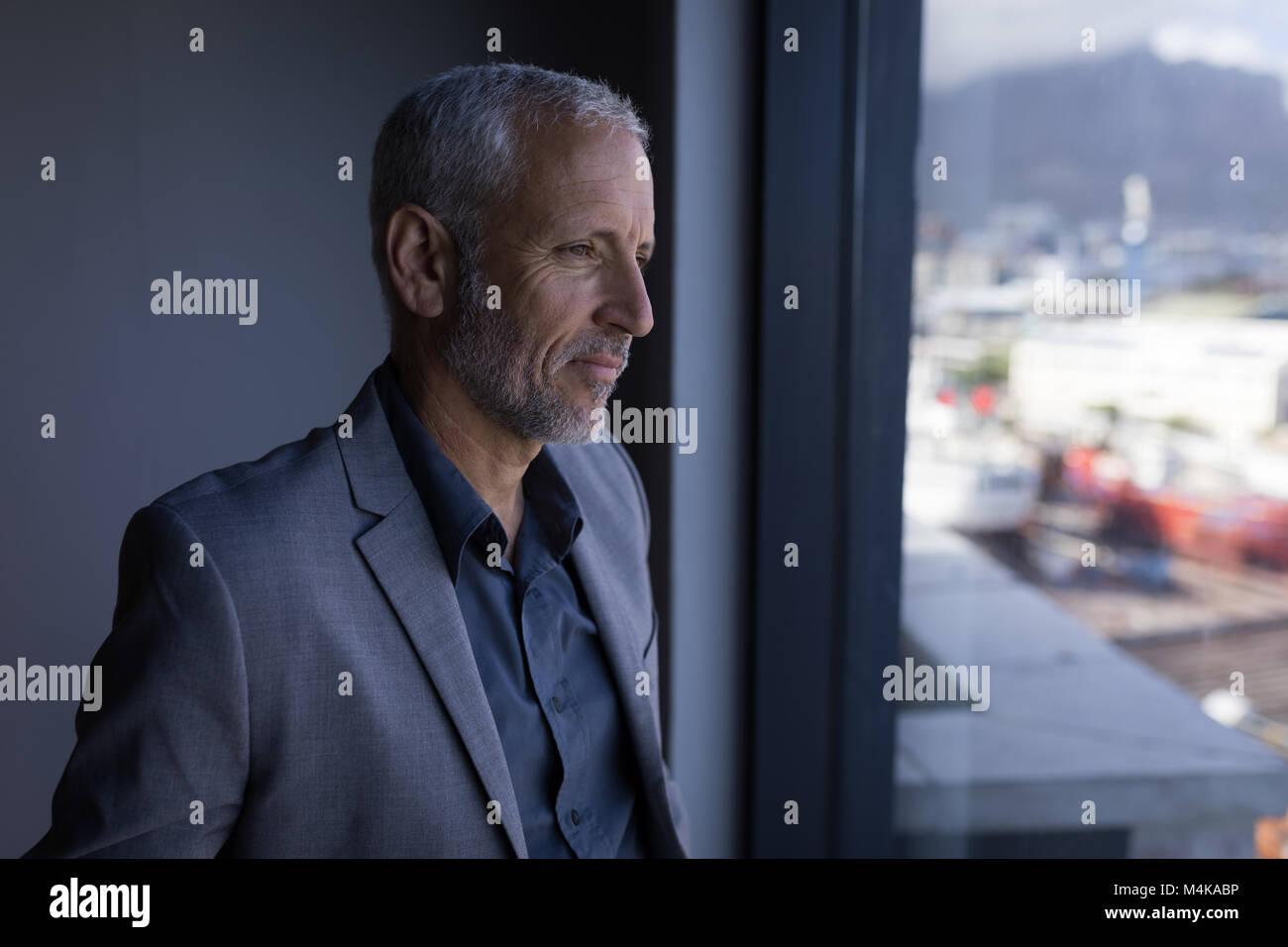 Business man guardando fuori della finestra Immagini Stock