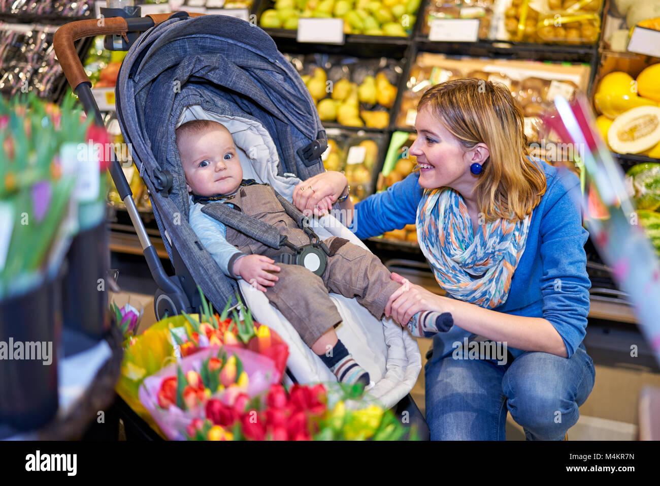 Giovane Donna con bambino figlio nel negozio di alimentari Immagini Stock