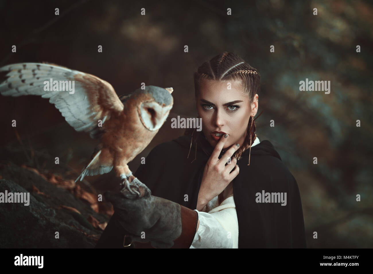 Donna con barbagianni sul suo braccio. Sfondo di foresta Foto Stock