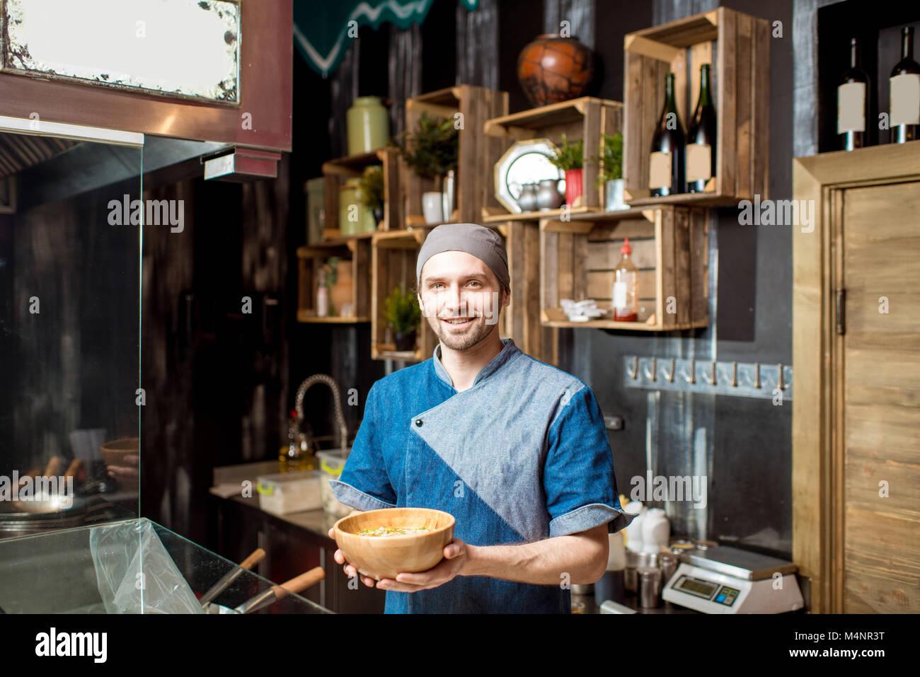 Il capo cuoco presso il ristorante asiatico cucina Immagini Stock