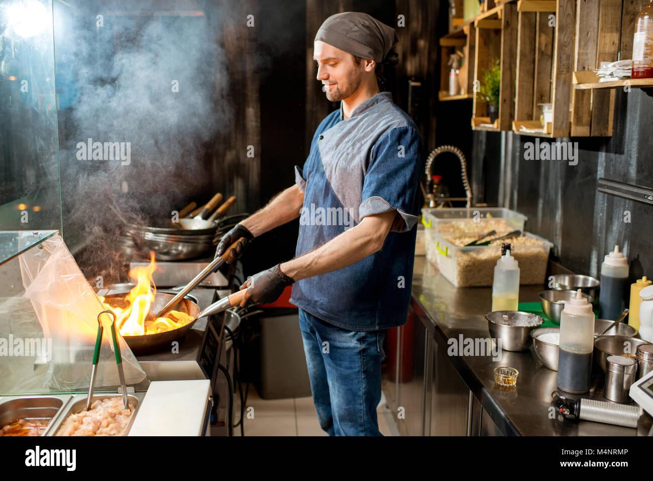 Il capo cuoco in cucina la cucina asiatica Immagini Stock