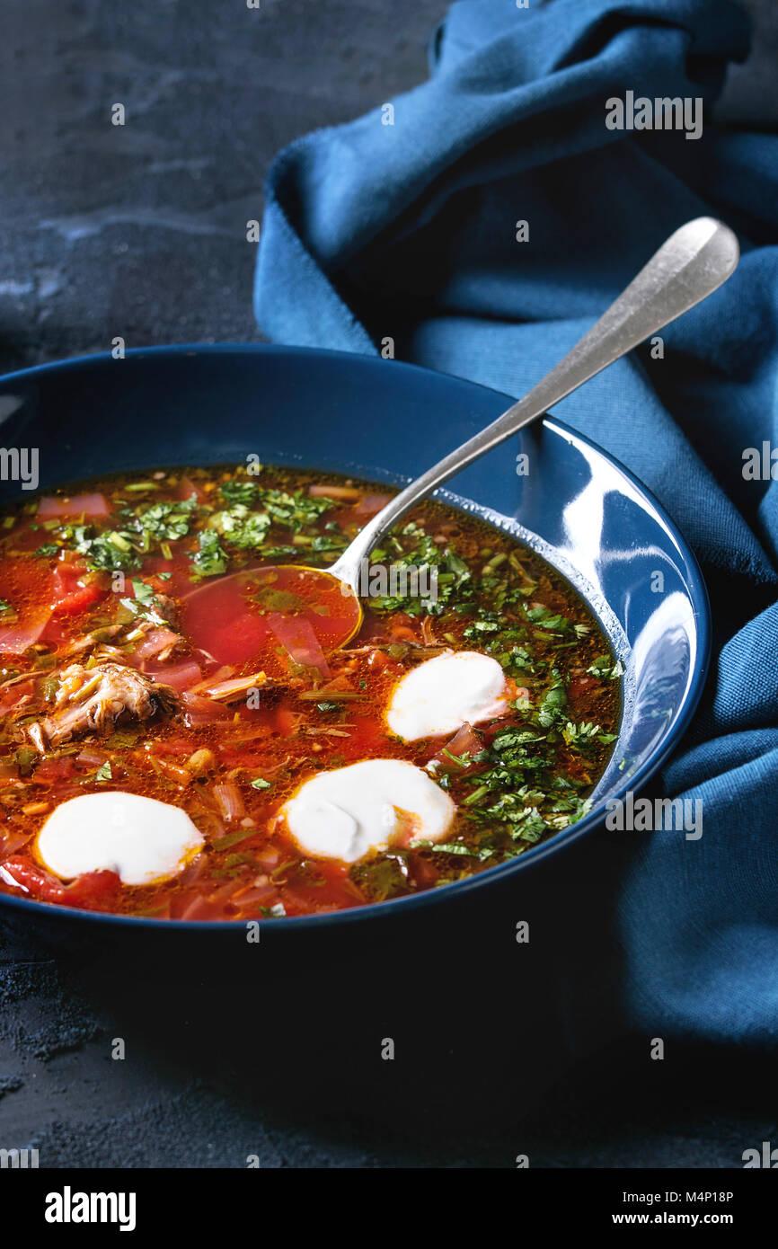 Piastra della barbabietola tradizionale zuppa borscht con panna acida e il coriandolo fresco servito con aglio pane Immagini Stock