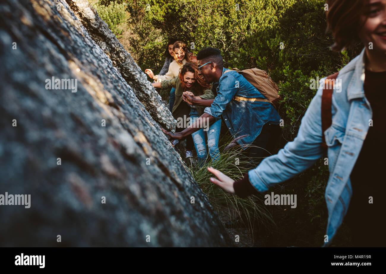 Giovani uomini e donne a piedi attraverso un sentiero di montagna. Giovani escursioni in montagna. Immagini Stock