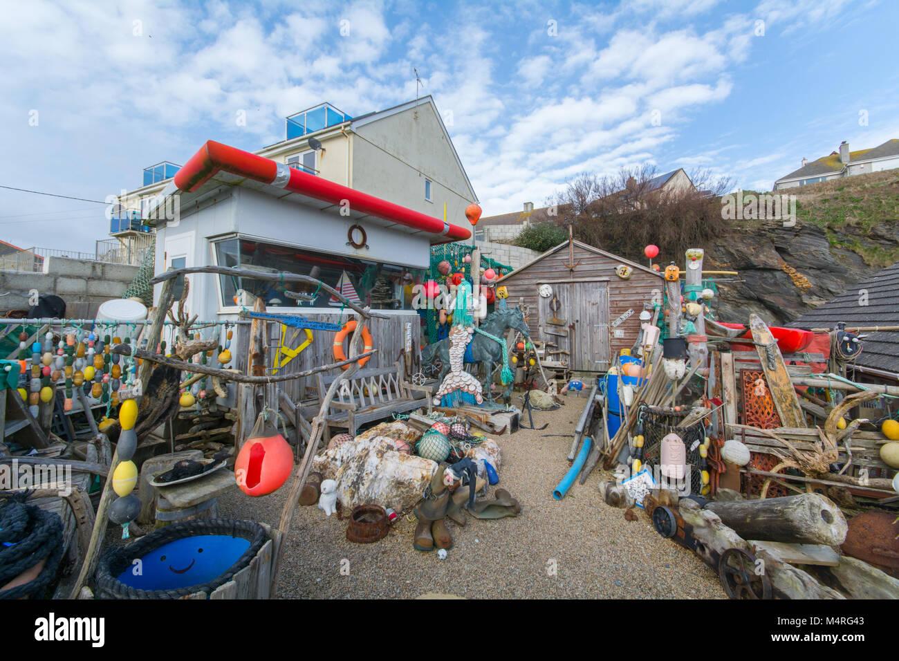 Bizzarre raccolta di elementi beachcombed e sculture in un cantiere nel centro di villeggiatura di Porthleven Cornovaglia Immagini Stock