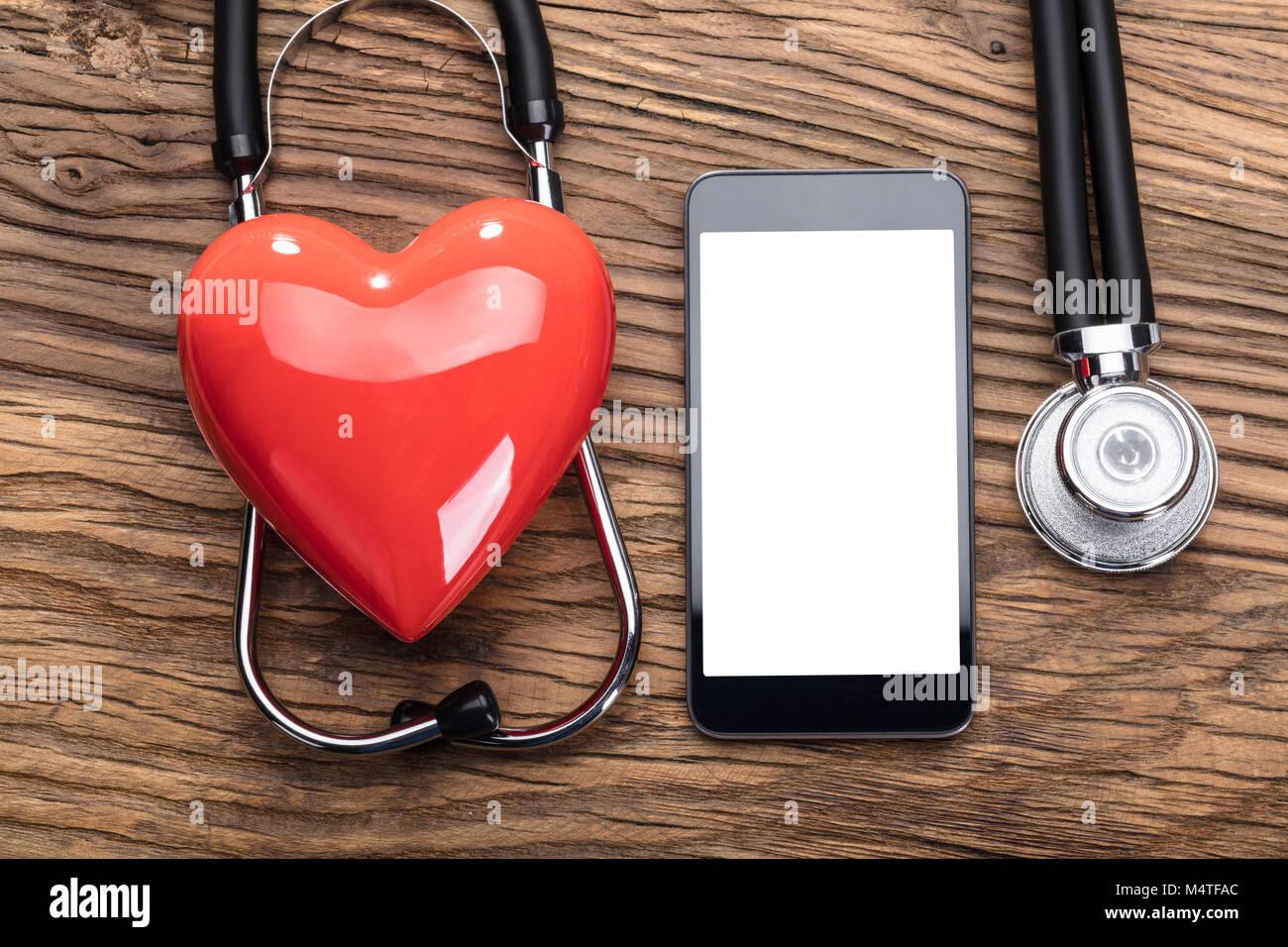Cuore rosso oltre lo stetoscopio con schermo vuoto Smart Phone sul tavolo di legno Immagini Stock
