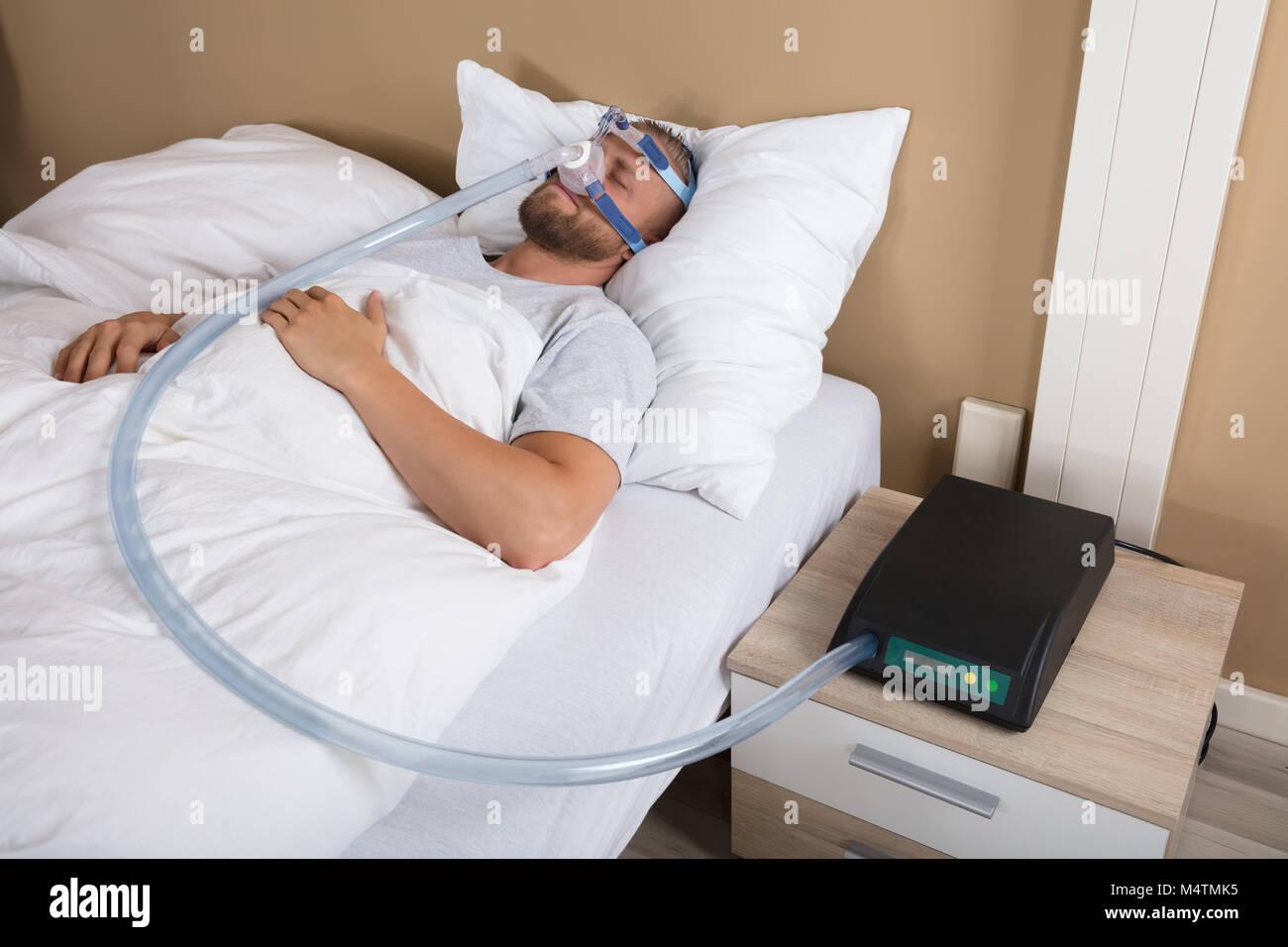 Giovane uomo disteso sul letto con apnea nel sonno e macchina CPAP Immagini Stock
