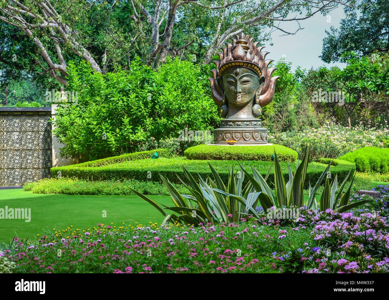 Vedica del giardino con vegetazione sottile, varieted striped fogliame, viola, annuari e un enorme di acciaio statua Immagini Stock