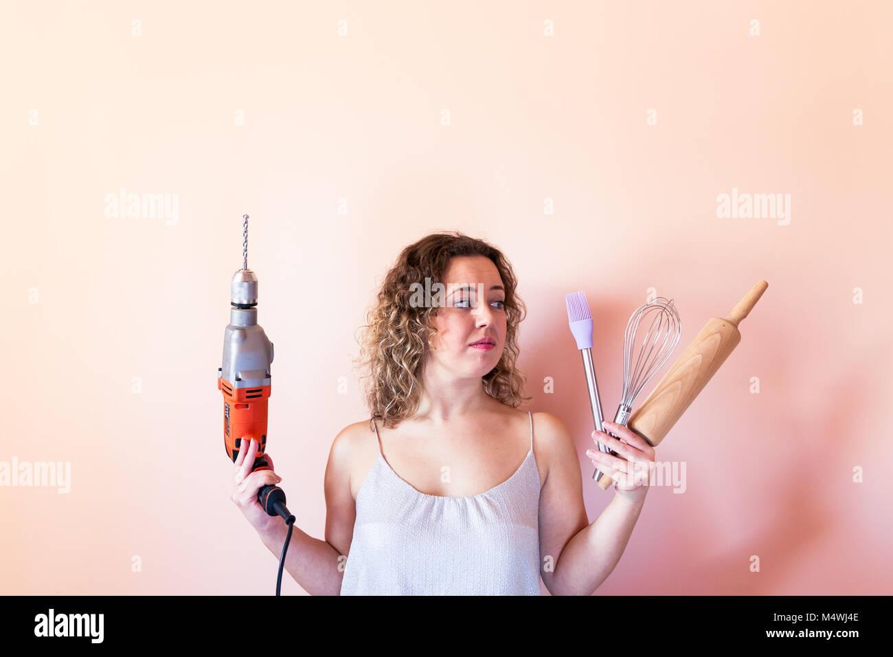 Bella donna ricci azienda uomo trapanatore e utensili per la cucina. La parità tra i sessi, la giornata della Immagini Stock