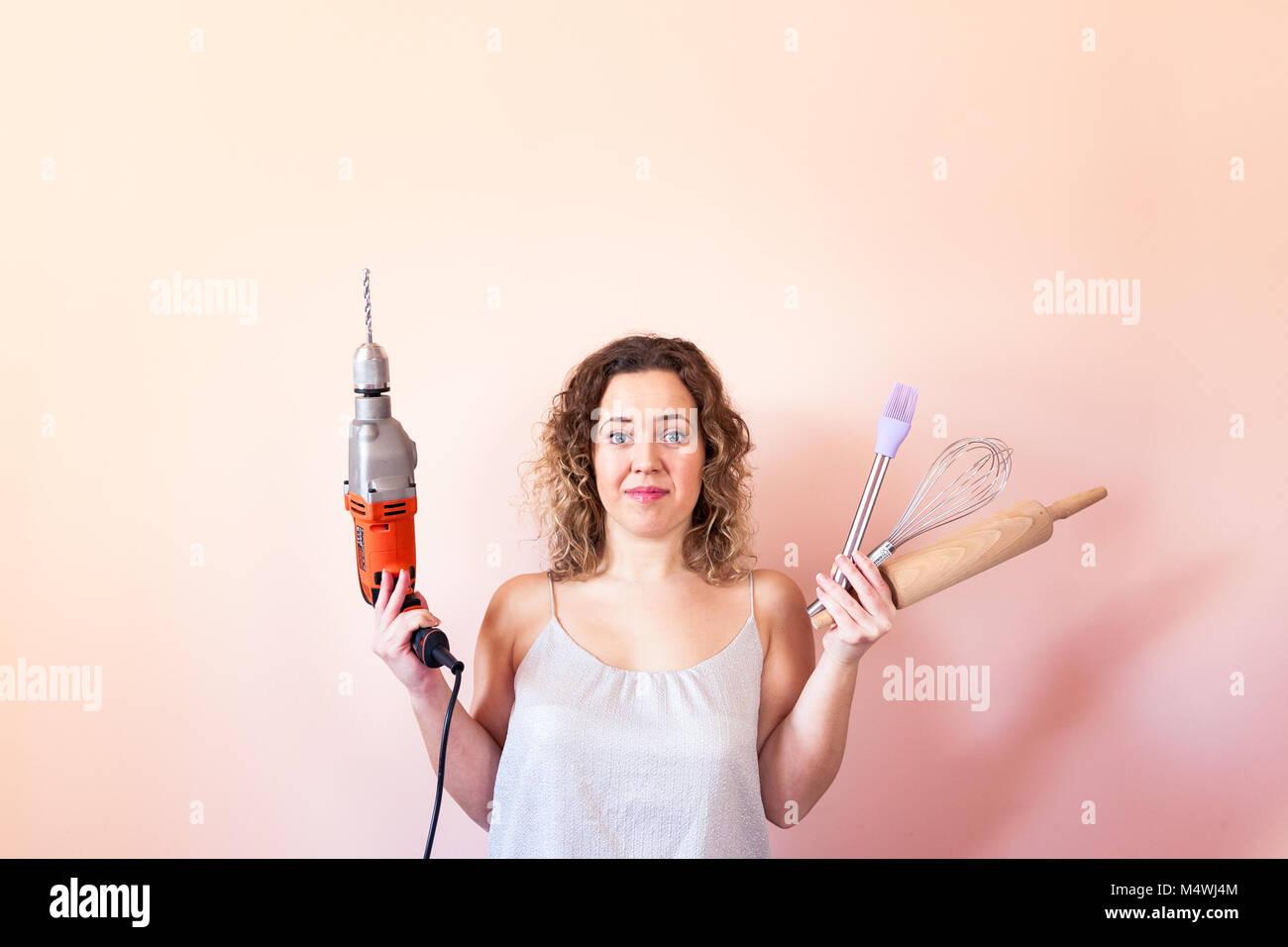 Bella donna ricci azienda uomo trapanatore e utensili per la cucina. La parità tra i sessi, la giornata della donna concetto. Foto Stock