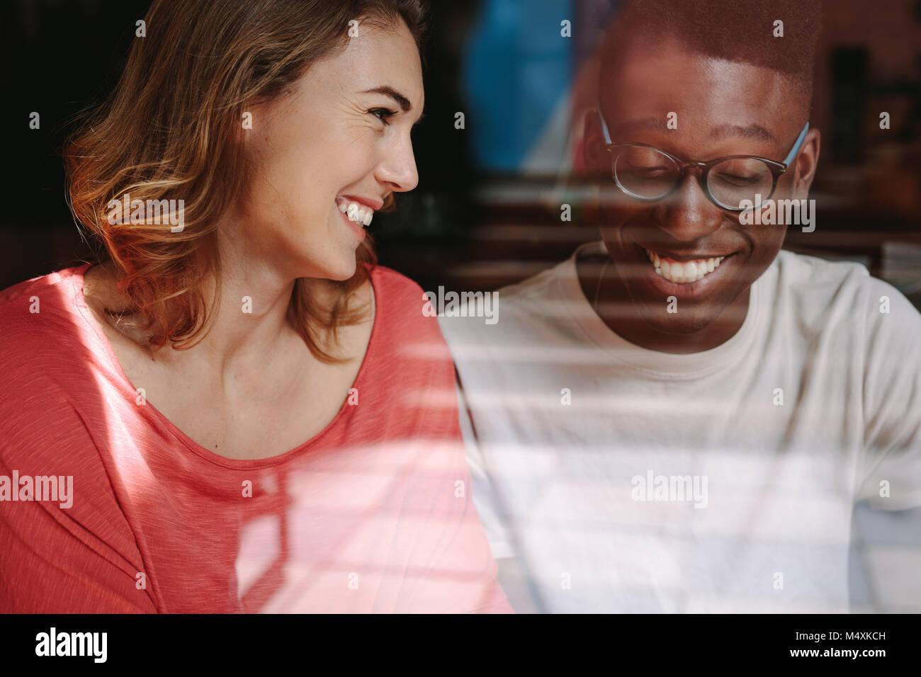 Donna sorridente guardando il suo amico in una caffetteria. Amici seduti ad un coffee shop e parlare. Foto Stock