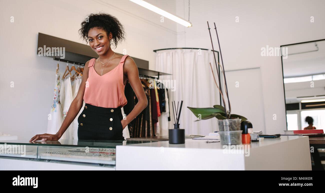 e95d1115556d Femmina designer di moda in piedi alla sua scrivania nella sua boutique.  Abito femminile designer