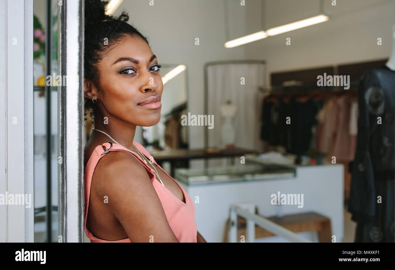 58733ea36a11 Femmina designer di moda in piedi nella sua boutique. Abito femminile designer  nel suo negozio di stoffa con abiti firmati sul display.