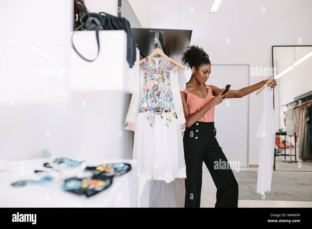 ebc748c46267 Designer di moda tenendo fotografia di un designer di sposa nel suo studio  di moda.