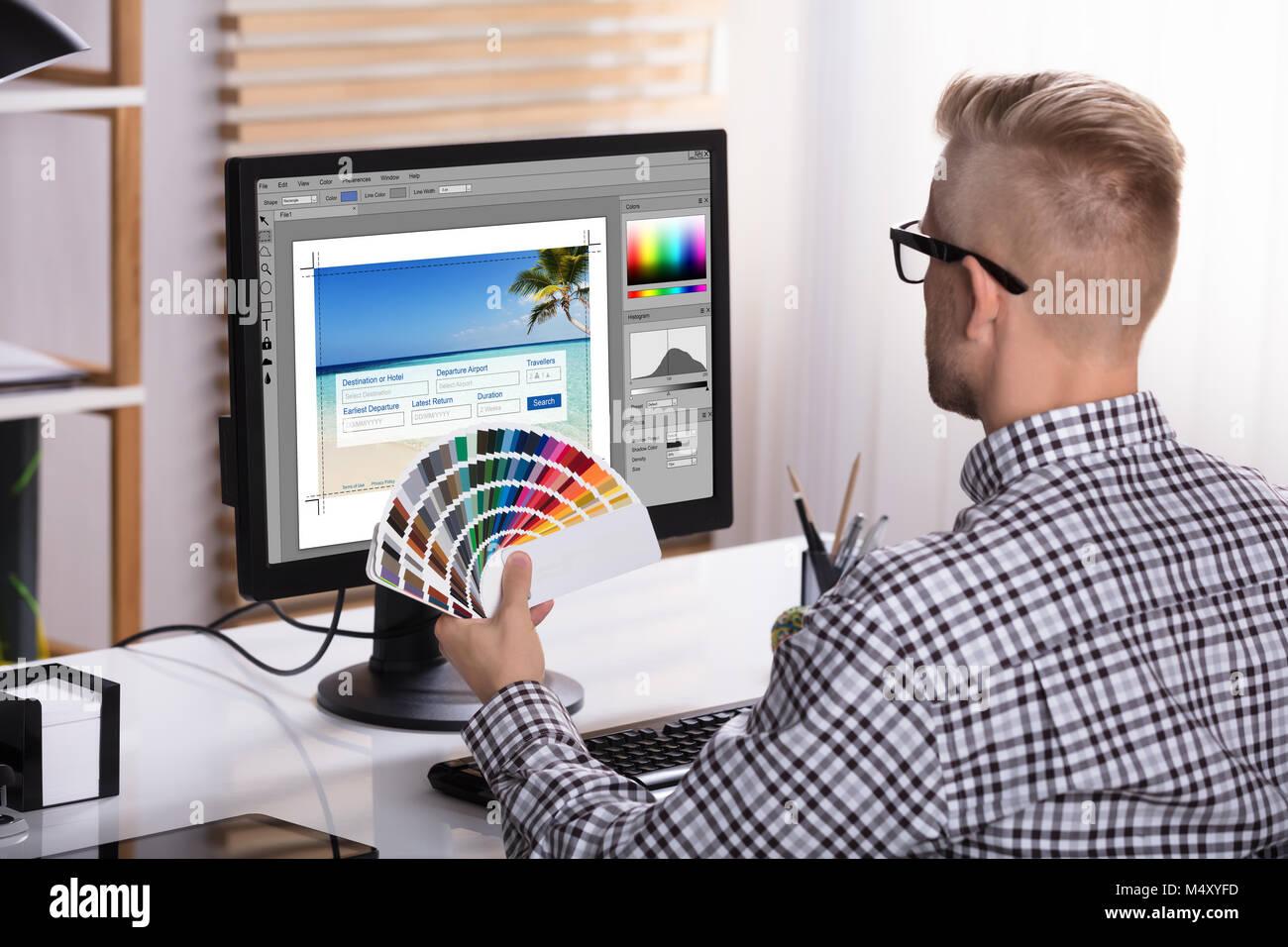 Un Designer maschio utilizzando Computer tenendo i campioni di colore in mano Immagini Stock