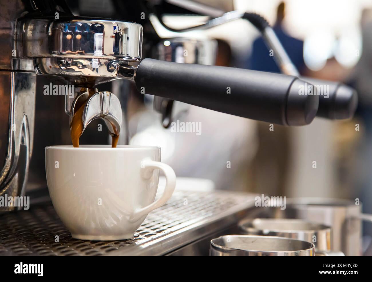 Chiusura del corso di caffè nella tazza da barista macchina nella caffetteria. Americano che sta per essere Immagini Stock