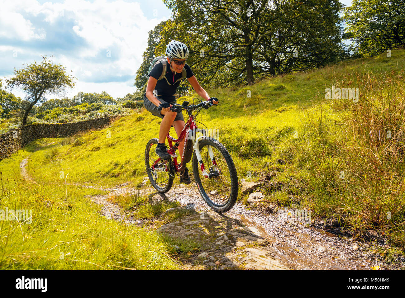 Femmina mountain biker sul sentiero vicino Winster nel Lake District inglese Immagini Stock