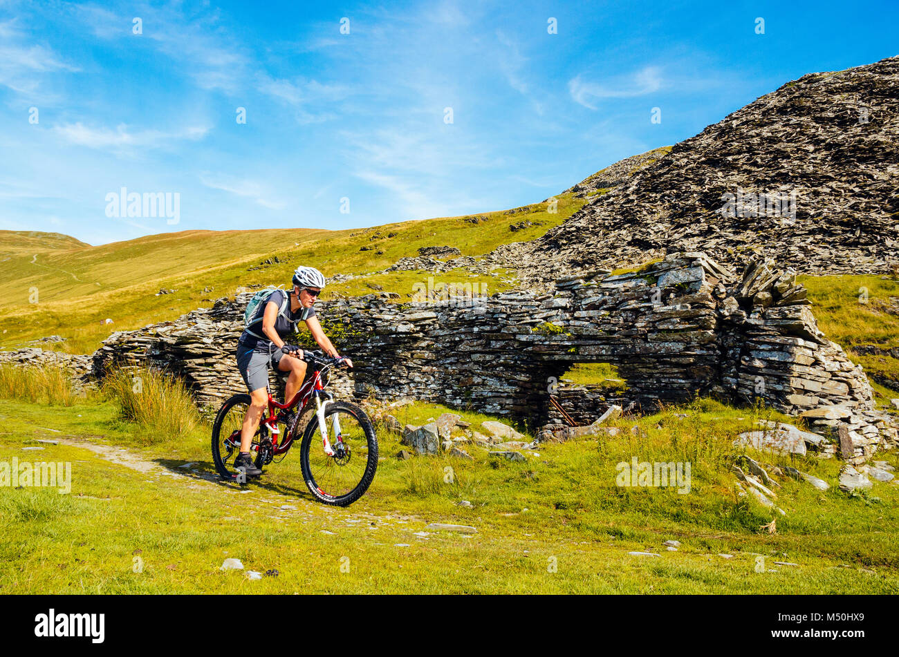 Femmina mountain biker passando le rovine di cava a Walna Scar cave nel Lake District inglese Immagini Stock
