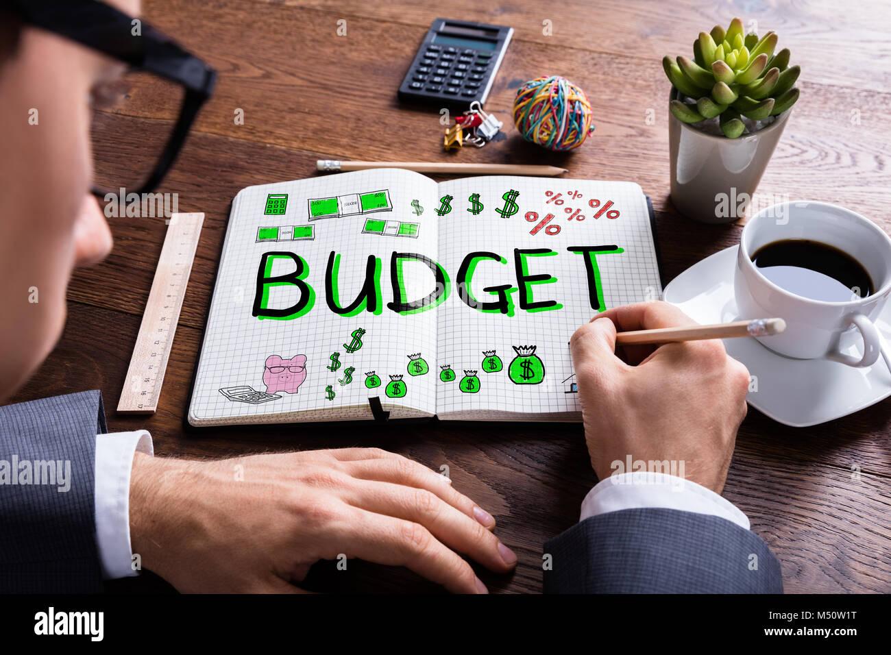 Disegno Uomo Alla Scrivania : Uomo di disegno piano di bilancio in notebook alla scrivania foto